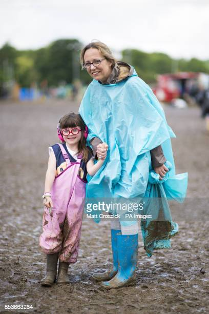 Festivalgoers Emma aged 6 and her mother Sarah from St Albans prepare for more wet weather at the Glastonbury Festival at Worthy Farm in Somerset