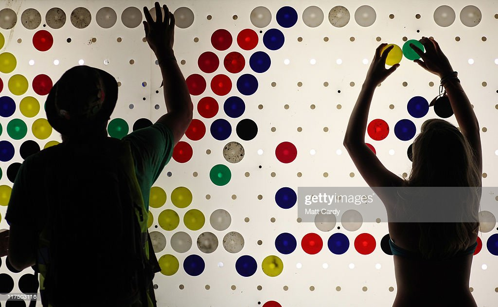 Festival-goers enjoy a visual game in the late night venue Shangri-La area at the Glastonbury Festival site at Worthy Farm, Pilton on June 27, 2011. This year's festival featured headline acts <a gi-track='captionPersonalityLinkClicked' href=/galleries/search?phrase=U2&family=editorial&specificpeople=201268 ng-click='$event.stopPropagation()'>U2</a>, Coldplay and Beyonce. The festival, which started in 1970 when several hundred hippies paid 1 GBP to watch Marc Bolan, has grown into Europe's largest music festival attracting more than 175,000 people over five days.