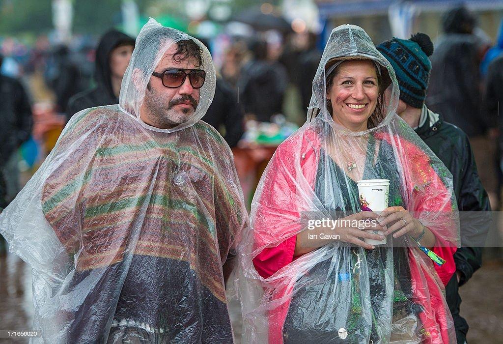 Festival-goers enjoy the atmosphere as rain falls during day 1 of the 2013 Glastonbury Festival at Worthy Farm on June 27, 2013 in Glastonbury, England.