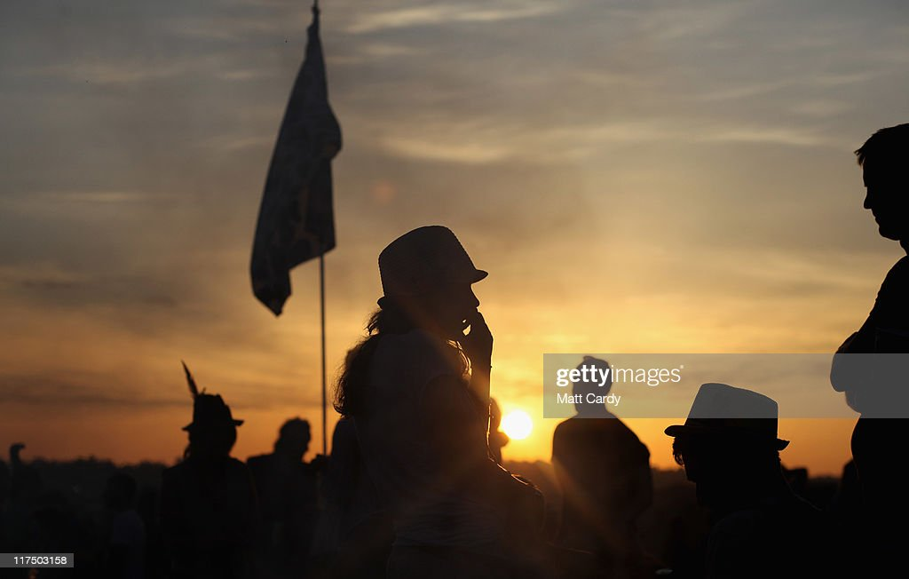 Festival-goers gather to see the sunrise from the Stone Circle area at the Glastonbury Festival site at Worthy Farm, Pilton on June 27, 2011. This year's festival featured headline acts U2, Coldplay and Beyonce. The festival, which started in 1970 when several hundred hippies paid 1 GBP to watch Marc Bolan, has grown into Europe's largest music festival attracting more than 175,000 people over five days.