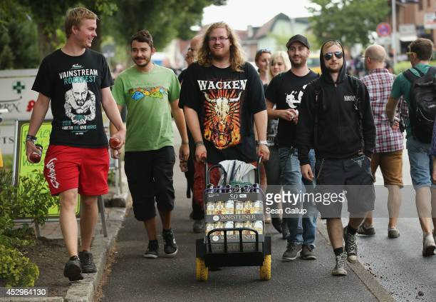 Festivalgoers head twoards the festival grounds after shopping for essentials at a local village grocery store at the 2014 Wacken Open Air heavy...