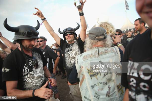 Festivalgoers listen to a band at a minor stage at the 2014 Wacken Open Air heavy metal music festival on the eve of the first official concerts on...