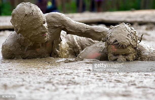 Festivalgoers plays in a mud pond created by students evoking the atmosphere of Woodstock during the 34th edition of the Paleo festival on July 22...