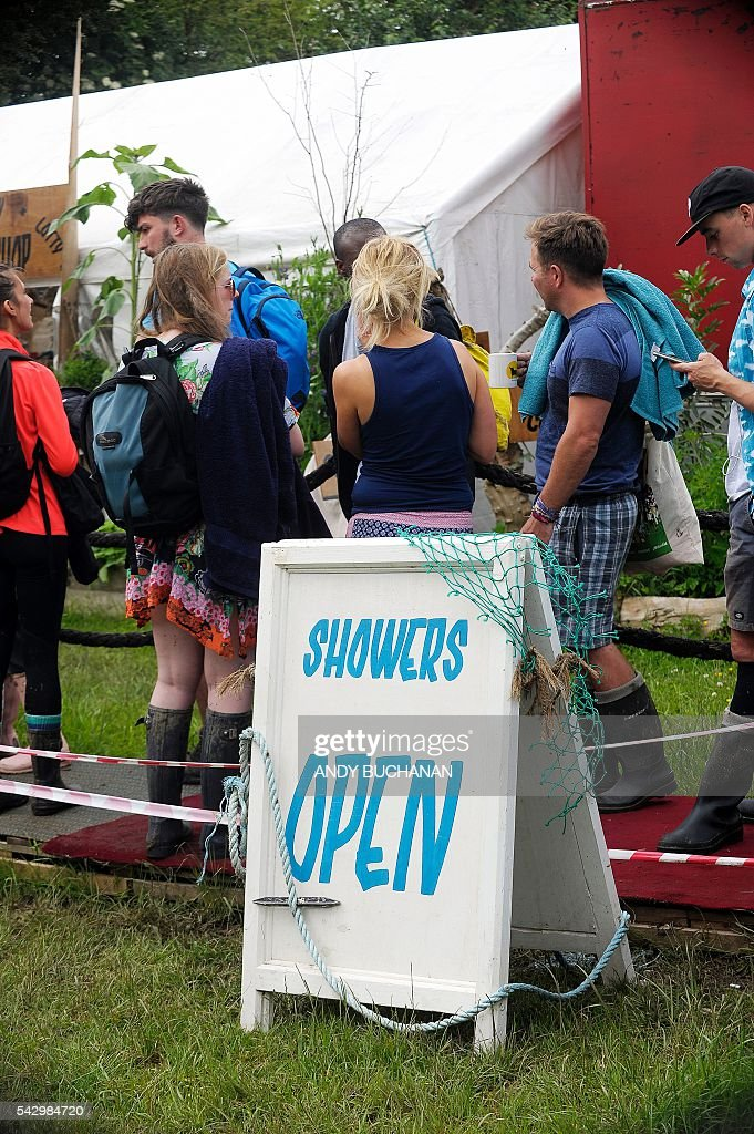 Festival-goers queue for the showers on day four of the Glastonbury Festival of Music and Performing Arts on Worthy Farm near the village of Pilton in Somerset, South West England on June 25, 2016. / AFP / Andy Buchanan