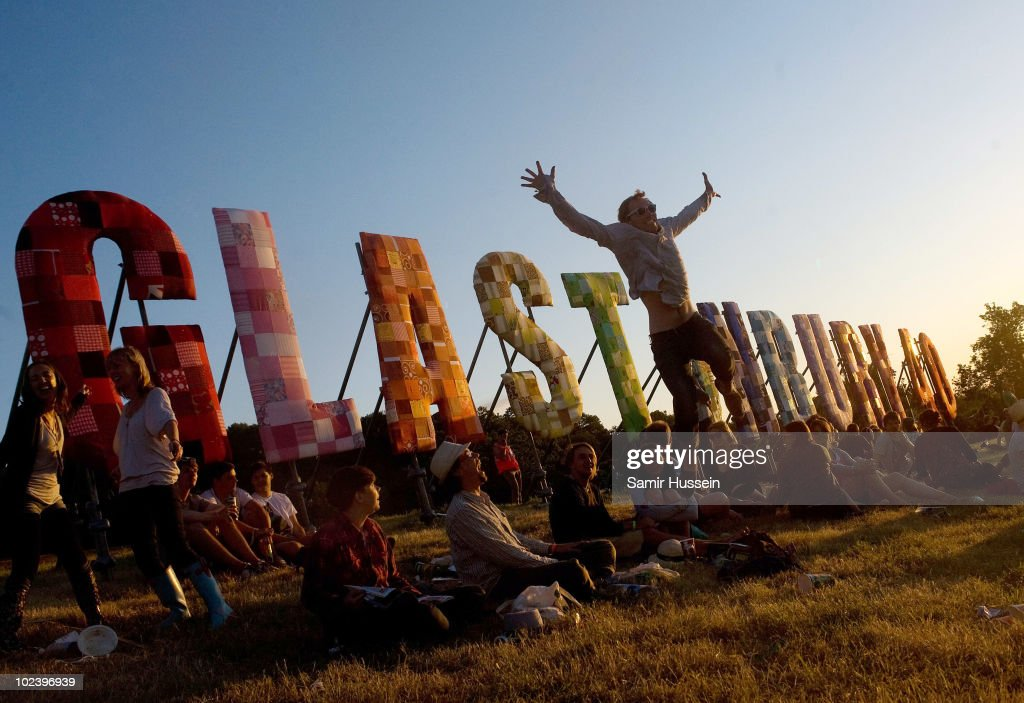 Festival-goers relax in front of the Glastonbury sign at the Glastonbury Festival on June 24, 2010 in Glastonbury, England. Glastonbury has become Europe's largest music festival and is celebrating its 40th anniversary.
