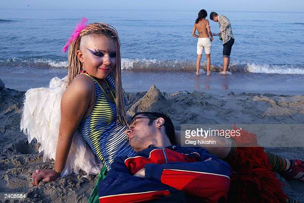 Festivalgoers relax in the morning sun at the annual youth musical festival August 18 2003 in Kazantip Ukraine The Kazantip annual youth musical...