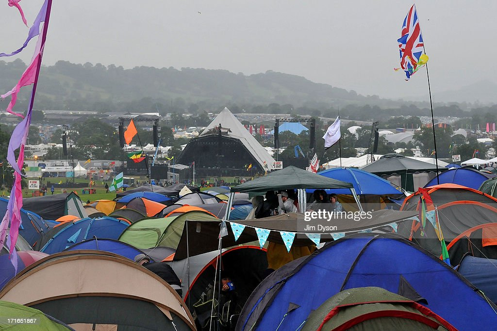 Festival-goers shelter from the rain as final preparations are made to the Pyramid stage during day 1 of the 2013 Glastonbury Festival at Worthy Farm on June 27, 2013 in Glastonbury, England.