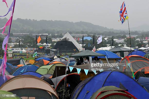 Festivalgoers shelter from the rain as final preparations are made to the Pyramid stage during day 1 of the 2013 Glastonbury Festival at Worthy Farm...