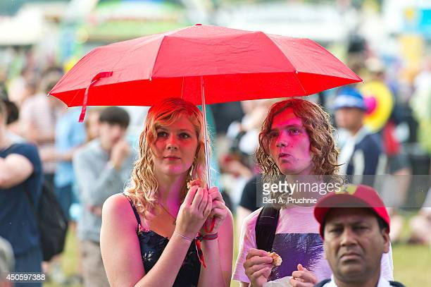 Festivalgoers shelter from the rain at The Isle of Wight Festival as Seaclose Park on June 13 2014 in Newport Isle of Wight