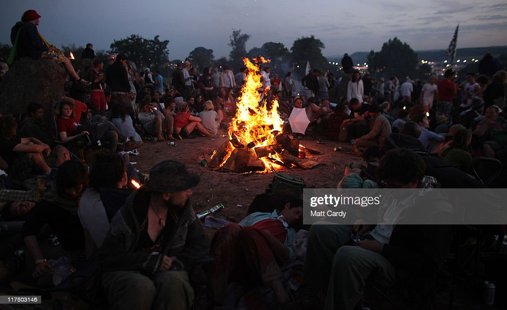 Festival-goers sit around a fire as they gather to see the sunrise from the Stone Circle area at the Glastonbury Festival site at Worthy Farm, Pilton on June 27, 2011. This year's festival featured headline acts U2, Coldplay and Beyonce. The festival, which started in 1970 when several hundred hippies paid 1 GBP to watch Marc Bolan, has grown into Europe's largest music festival attracting more than 175,000 people over five days.