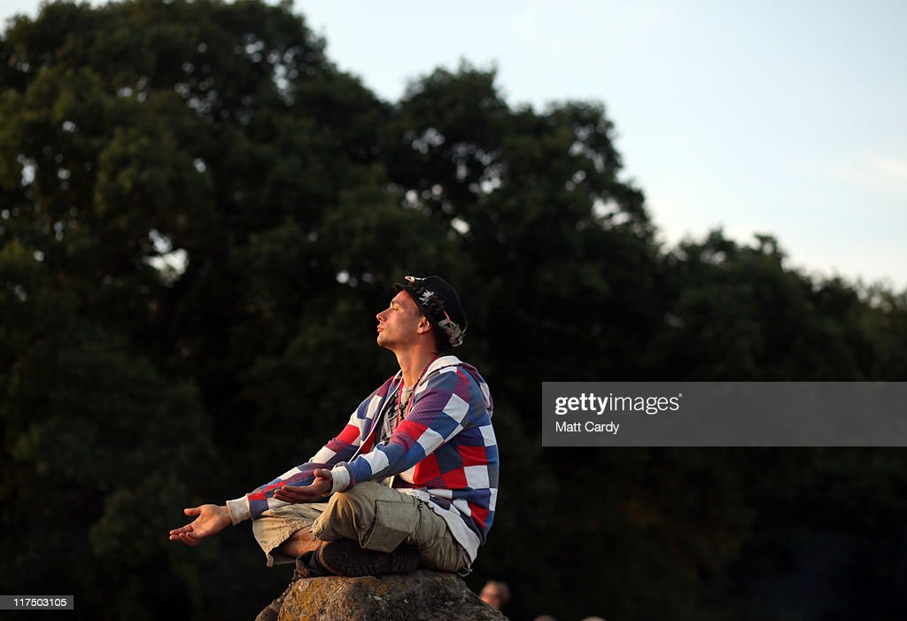 A festival-goers sits on a stone as he gathers to see the sunrise from the Stone Circle area at the Glastonbury Festival site at Worthy Farm, Pilton on June 27, 2011. This year's festival featured headline acts U2, Coldplay and Beyonce. The festival, which started in 1970 when several hundred hippies paid 1 GBP to watch Marc Bolan, has grown into Europe's largest music festival attracting more than 175,000 people over five days.