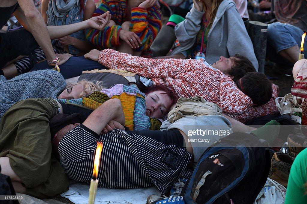 Festival-goers sleep as they wait to see the sunrise from the Stone Circle area at the Glastonbury Festival site at Worthy Farm, Pilton on June 27, 2011. This year's festival featured headline acts U2, Coldplay and Beyonce. The festival, which started in 1970 when several hundred hippies paid 1 GBP to watch Marc Bolan, has grown into Europe's largest music festival attracting more than 175,000 people over five days.