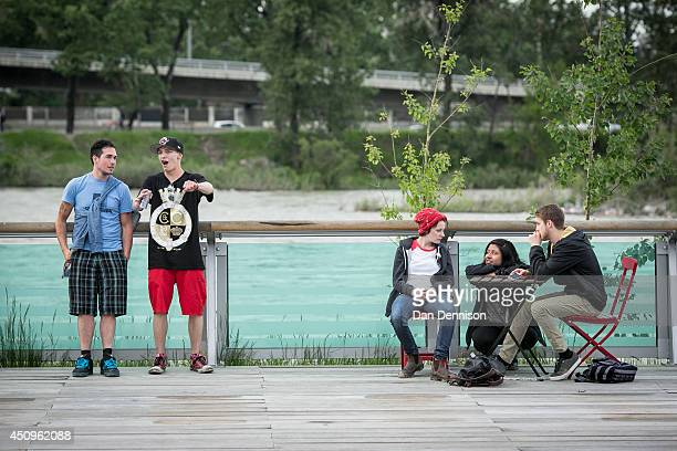 Festivalgoers take a break on the banks of the Bow River Calgary at the East Village Block Party during Sled Island Festival on June 19 2014 in...
