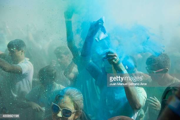 Festivalgoers throw colored powder during the Holi Festival of Colours at on September 21 2014 in Santander Spain