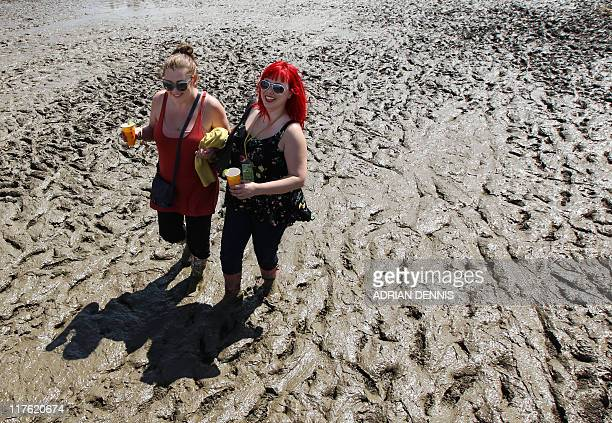 Festivalgoers walk through the mud at the Glastonbury festival near Glastonbury Somerset on June 23 2011 Veteran Irish band U2 are set to rock the...
