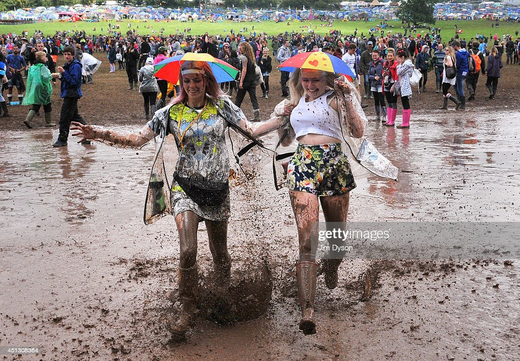 Festivalgoers walk through the mud during Day One of the Glastonbury Festival at Worthy Farm in Pilton on June 27 2014 in Glastonbury England Tickets...