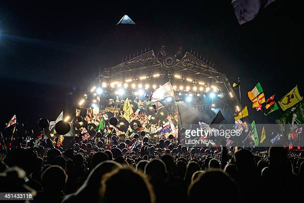 Festivalgoers watch US metal band Metallica perform on the Pyramid Stage on the second day of the Glastonbury Festival of Music and Performing Arts...