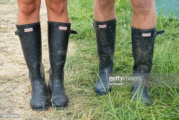 Festivalgoers wear wellington boots in preparation for rain during the Glastonbury Festival at Worthy Farm on June 26 2014 in Glastonbury England