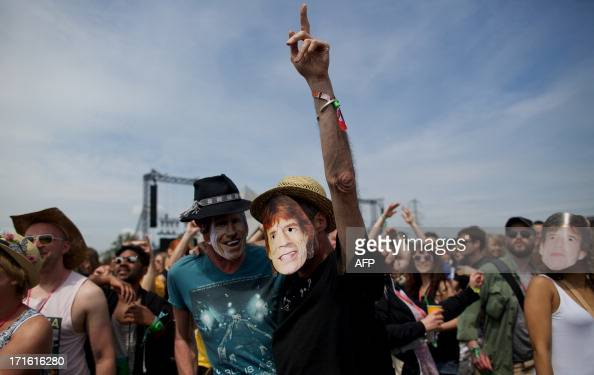 Festivalgoer's wearing masks of Rolling Stones singer Mick Jagger and guitarist Kieth Richards as they dance beside the Pyramid stage on the second...