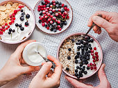 Festive and healthy breakfast for loved ones. Vintage bowls, cornflakes, granola, yogurt, fresh berries and hands of a young couple. Close-up, top view. Concept of healthy and delicious food