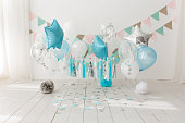 Festive background decoration for birthday celebration with gourmet cake and blue balloons in studio, cake smash first year concept.