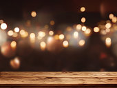 Festive background with light spots and bokeh in front of a empty wooden table