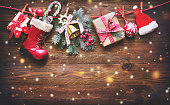 Festive background with Christmas presents, Santas accessories and decoration on the clothesline in front of wooden board. Top view