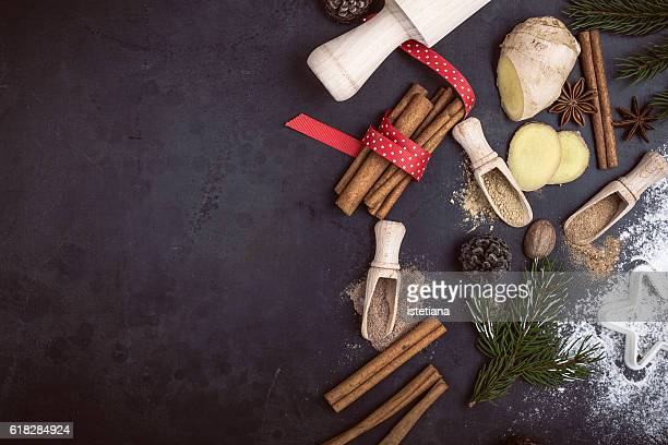 Festive border of traditional Christmas spices and cookies ingredients over rustic background with copyspace, top view