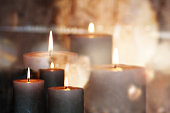 Burning candles in front of a festive background