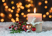 Burning candle with Christmas decor and festive lights.