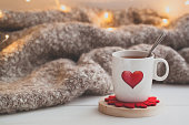 Festive Cup of tea with a smoke and a red heart over the knitted plaid. Toned