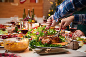 Female hands cutting chicken at Christmas dinner table