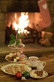 Photograph of a table set for afternoon tea at Christmas time. There is a three tiered cake stand containing sandwiches, Christmas cake, miniature stollens and cup cakes. At the top is a sprig of holl