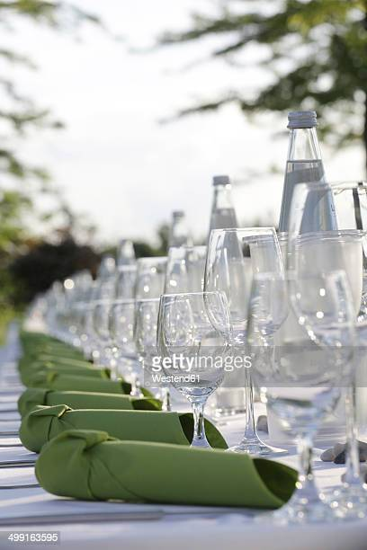 Festive laid table with green napkins, water bottles and wine glasses