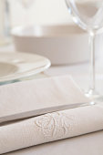 Festive laid table with monogram on white cloth napkin