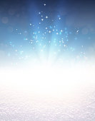 Blue colored light explosion and glittering stars on a snow covered ground