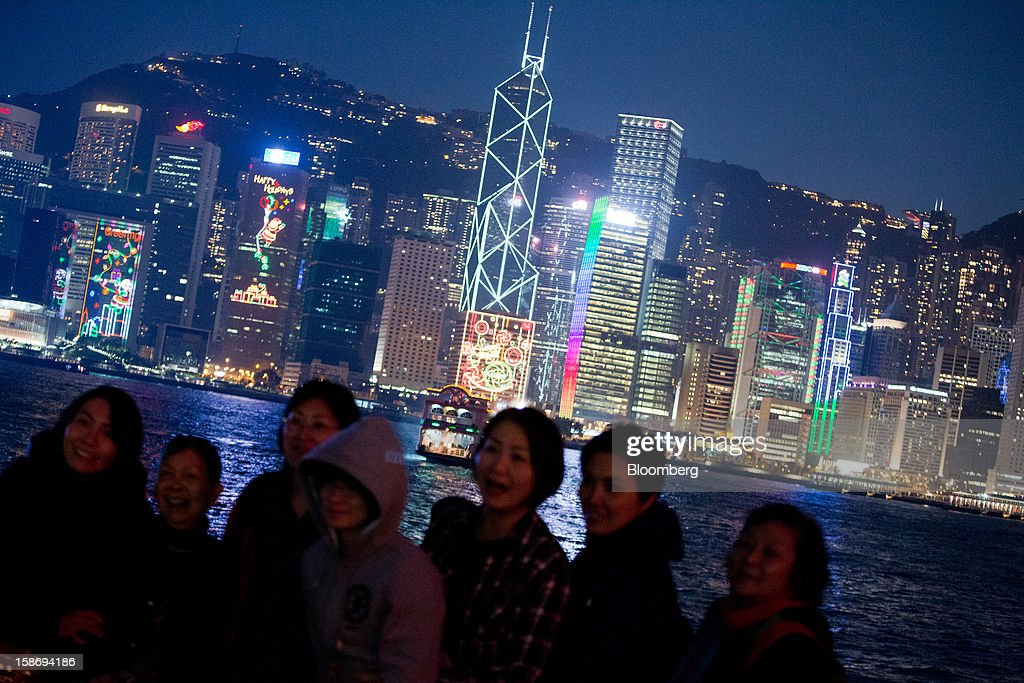Festive lights illuminate the city skyline as people pose for photographs on the waterfront promenade in the Tsim Sha Tsui area of Hong Kong, China, on Saturday, Dec. 22, 2012. Hong Kong's economy is set for its weakest annual expansion since the global financial crisis as the European sovereign debt crisis damps global trade. Photographer: Lam Yik Fei/Bloomberg via Getty Images