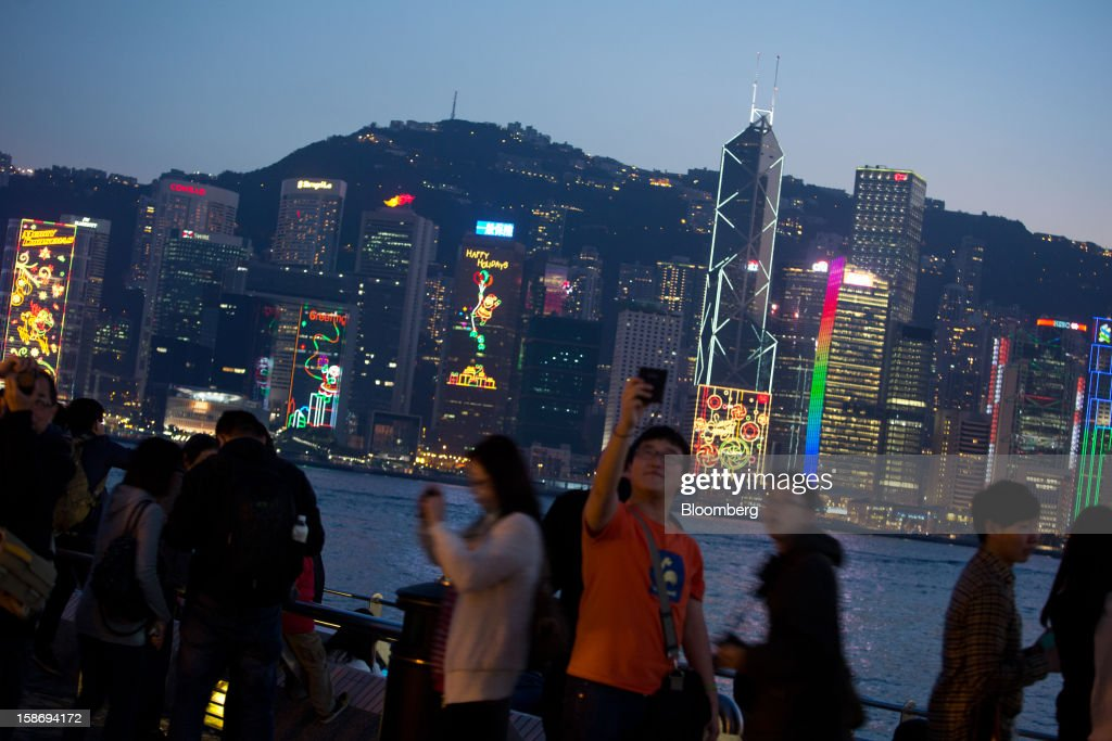 Festive lights illuminate the city skyline as people take photographs on the waterfront promenade in the Tsim Sha Tsui area of Hong Kong, China, on Saturday, Dec. 22, 2012. Hong Kong's economy is set for its weakest annual expansion since the global financial crisis as the European sovereign debt crisis damps global trade. Photographer: Lam Yik Fei/Bloomberg via Getty Images