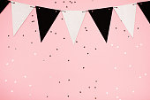 Festive background made of decorative flags and little stars, flat lay. Pink trend background with little silver stars on it. Flat lay style.