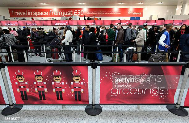 Festive 'Seasons Greetings' posters sit on the queue line barriers of the Virgin Atlantic checkin area at the south terminal of Gatwick airport in...