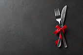 Festive set of cutlery knife and fork with red satin bow, dark stone slate concrete background, top view, copyspace.