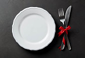 Festive set of cutlery knife and fork with red satin bow with a white dessert plate, dark stone slate background, top view, copyspace