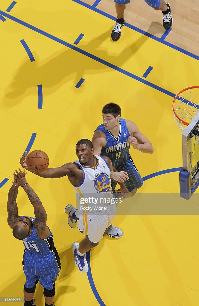 <a gi-track='captionPersonalityLinkClicked' href=/galleries/search?phrase=Festus+Ezeli&family=editorial&specificpeople=5725219 ng-click='$event.stopPropagation()'>Festus Ezeli</a> #31 of the Golden State Warriors rebounds against <a gi-track='captionPersonalityLinkClicked' href=/galleries/search?phrase=Jameer+Nelson&family=editorial&specificpeople=202057 ng-click='$event.stopPropagation()'>Jameer Nelson</a> #14 and Nikola Vecevic of the Orlando Magic on December 3, 2012 at Oracle Arena in Oakland, California.