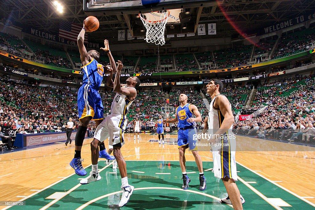 Festus Ezeli #30 of the Golden State Warriors rises for a dunk against Jeremy Evans #40 of the Utah Jazz at Energy Solutions Arena on February 19, 2013 in Salt Lake City, Utah.