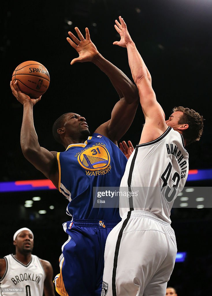Festus Ezeli #31 of the Golden State Warriors takes a shot as Kris Humphries #43 of the Brooklyn Nets defends on December 7, 2012 at the Barclays Center in the Brooklyn borough of New York City.