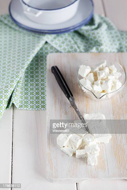 Feta cheese with knife on chopping board, close up