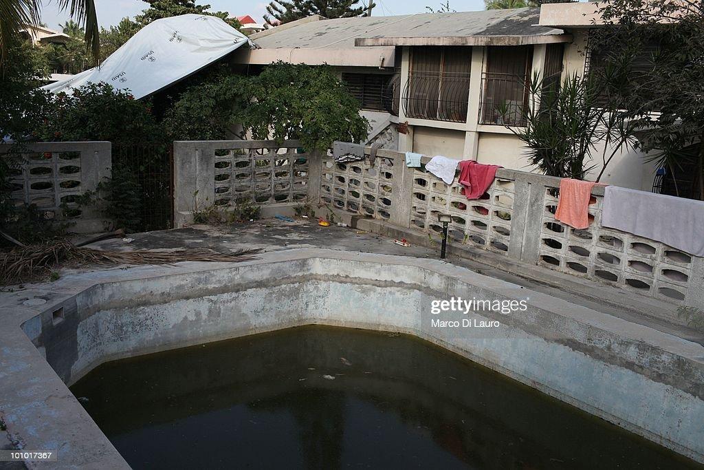A fetid swimming pool is covered with a cloud of mosquitoes at the Faith Hope Love Infant Rescue Orphanage managed by a US citizen named Dorothy Pearce on February 4, 2010 in Port Au Prince, Haiti. Dorothy Pearce a US Citizen founded the Faith Hope Love Infant Rescue five years ago answering what she describes as a 'call by God' to leave her job as a real estate agent in Miami to come to Haiti. She runs the organization from her home in Port-au-Prince taking in children whose families are unable to support them. She is currently caring for 20 children. In the backyard strewn with rubbish, ten babies lie sleeping on the dirty concrete floor under a canopy of plastic sheeting, many are newborn. The older children play largely unobserved by the nannies barefoot amongst rusted tins and dirty nappies. A fetid swimming pool is covered with a cloud of mosquitoes. Three dogs, whose feces litter the small concrete play area, lick the children's faces as they play and lie on the floor. Several of the children are HIV positive and many suffer with severe disabilities. Most of the children appear listless, either clamouring to be held or curled up sleeping awkwardly on the floor. Others sit crying, unattended. One of the children, Alexandra, 2, was injured in the earthquake. Pearce who has not received any medical training, cuts dead flesh from an open wound on the injured child's foot as she screams in agony. Pearce has not registered her charity with the Haitian government and the orphanage is entirely unregulated. Prior to the earthquake that devastated the island on January 12th, there were an estimated 380,000 children living in orphanages in Haiti, 500 of which were unregistered. Since the disaster, in which thousands of children were separated from their families, the dangers facing Haiti's orphans have never been more acute.