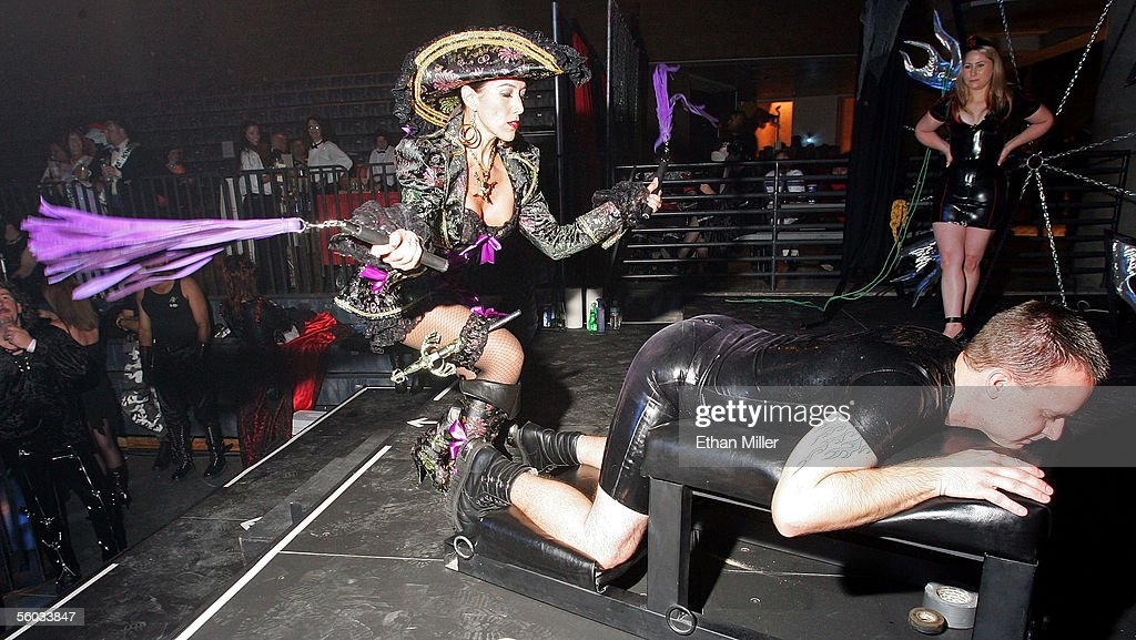 Fetish model and artist Ms. Veronique of California (L) flogs David Larson of California as his wife Lisa Larson (R) watches on the exhibitionist stage during the 10th annual Fetish & Fantasy Halloween Ball at the Las Vegas Sports Center on October 29, 2005 in Las Vegas, Nevada.