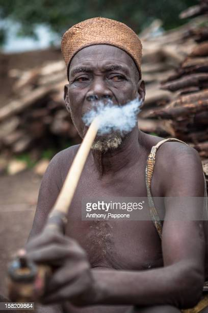 fetish priest in the village of Taneka Beri smokes a pipe traditional meter long Atakora region in northern Benin
