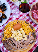 Elements of Italian and Roman traditional cuisine, such as gnocchi, fettuccine, eggs. Flavors and colors of the Italian tradition, such as prosciutto (ham) and mollusc dishes (at the corner of the pho